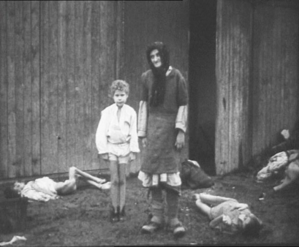 Auschwitz: Little girl and woman stand amongst dead bodies.